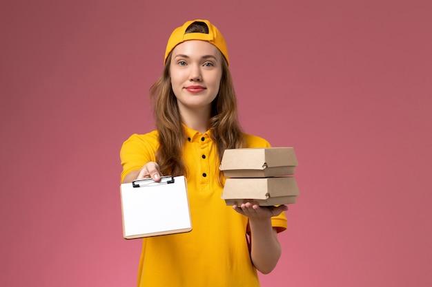 Corriere femminile di vista frontale in uniforme gialla e mantello che tiene piccoli pacchetti di cibo di consegna con il blocco note sul lavoratore uniforme di consegna di servizio della parete rosa