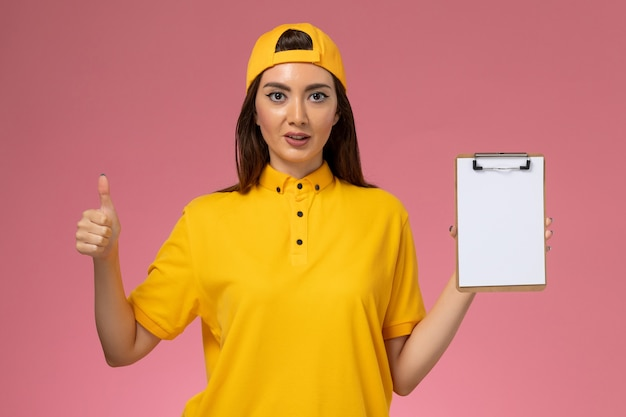 Corriere femminile di vista frontale in uniforme gialla e blocco note della tenuta del capo sulla consegna dell'uniforme di servizio dell'azienda della parete rosa