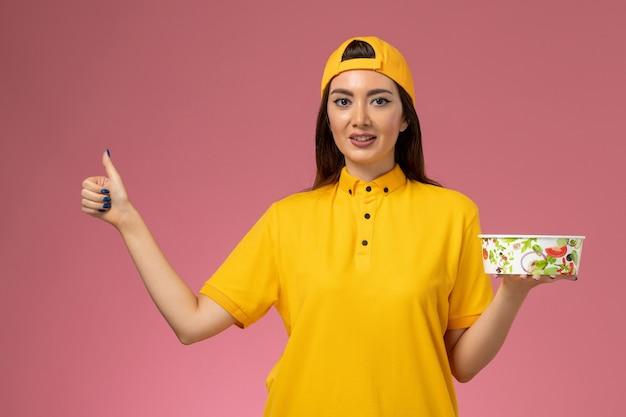 Corriere femminile di vista frontale in uniforme gialla e mantello che tiene la ciotola di consegna rotonda sul lavoro di consegna dell'uniforme di servizio della parete rosa
