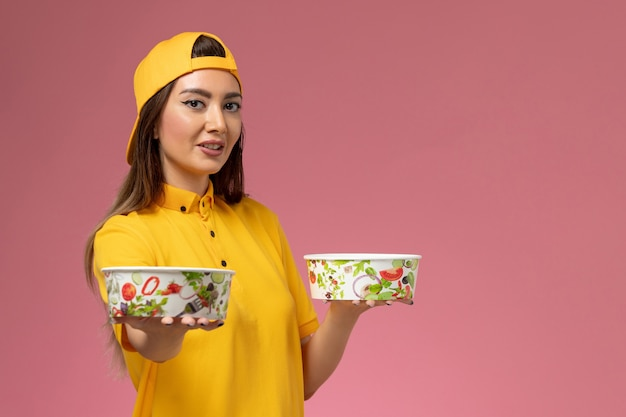 Front view female courier in yellow uniform and cape holding round delivery bowls on pink wall service uniform delivery job work