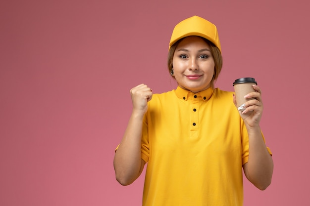 Front view female courier in yellow uniform yellow cape holding coffee cup on the pink desk uniform delivery female