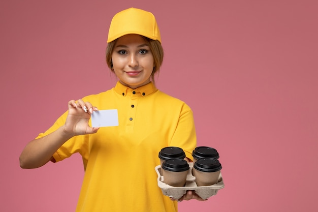 Front view female courier in yellow uniform yellow cape holding coffee cups and card on pink background uniform delivery work color job