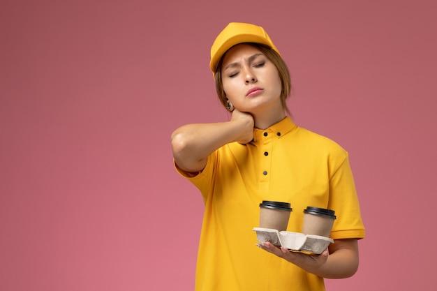 Corriere femminile di vista frontale in mantello giallo uniforme giallo che tiene tazze di caffè con mal di collo sul lavoro di lavoro di consegna uniforme sfondo rosa Foto Gratuite