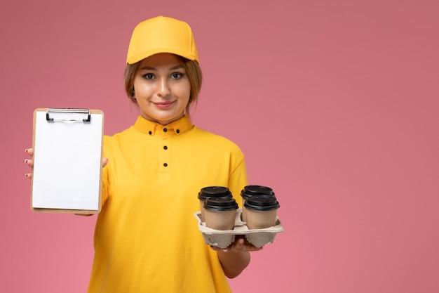 Corriere femminile di vista frontale in capo giallo uniforme giallo che tiene il blocco note delle tazze di caffè sul lavoro di colore del lavoro di consegna uniforme del fondo rosa