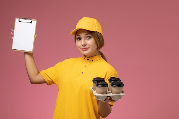 Front view female courier in yellow uniform yellow cape holding coffee cups and notepad on the pink background uniform delivery work job color