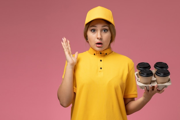 Front view female courier in yellow uniform yellow cape holding coffee cups on pink background uniform delivery work color job