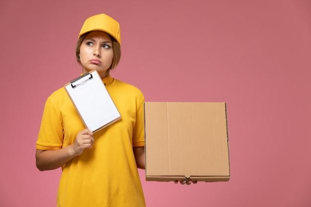 Corriere femminile di vista frontale nel blocchetto per appunti della scatola di cibo della tenuta del mantello giallo uniforme giallo sul colore femminile di consegna uniforme della scrivania rosa