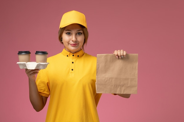 Front view female courier in yellow uniform yellow cape holding food package and coffee cups on pink desk uniform delivery female work color