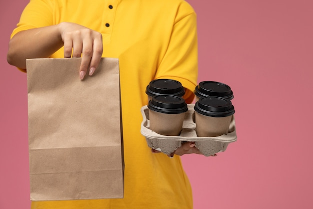 Front view female courier in yellow uniform yellow cape holding food package and coffee on the pink background uniform delivery work job color