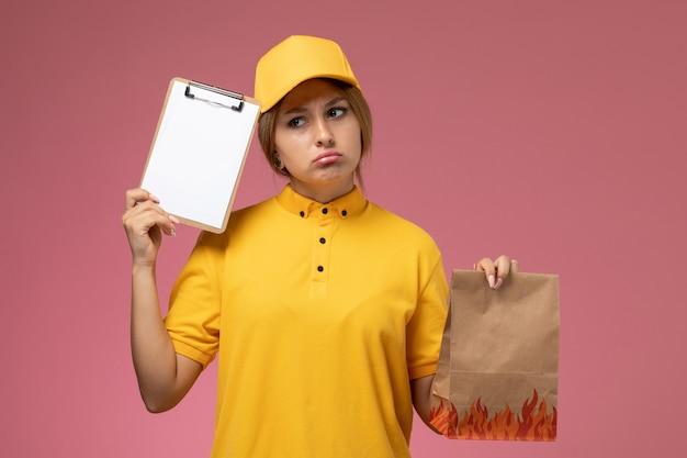 Corriere femminile di vista frontale in capo giallo uniforme giallo che tiene il pacchetto di cibo e il blocco note pensando sul lavoro di colore del lavoro di consegna uniforme del fondo rosa