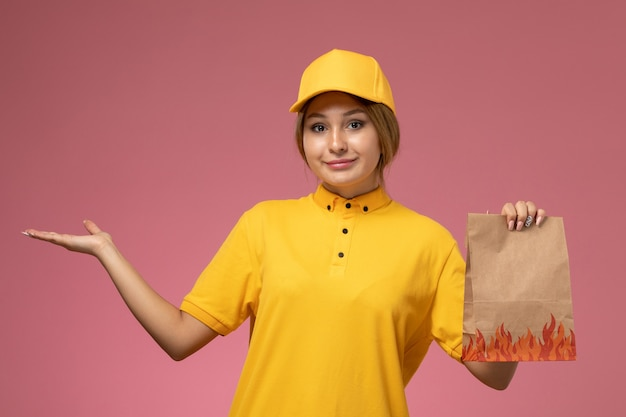 Front view female courier in yellow uniform yellow cape holding food package on pink background uniform delivery work color