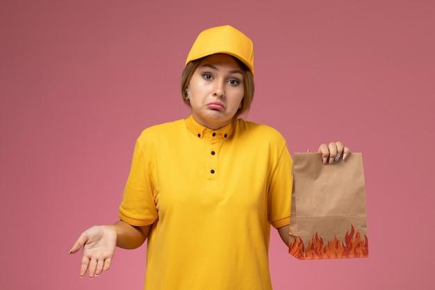 Corriere femminile di vista frontale in mantello giallo uniforme giallo che tiene il pacchetto alimentare sul colore del lavoro di consegna uniforme sfondo rosa