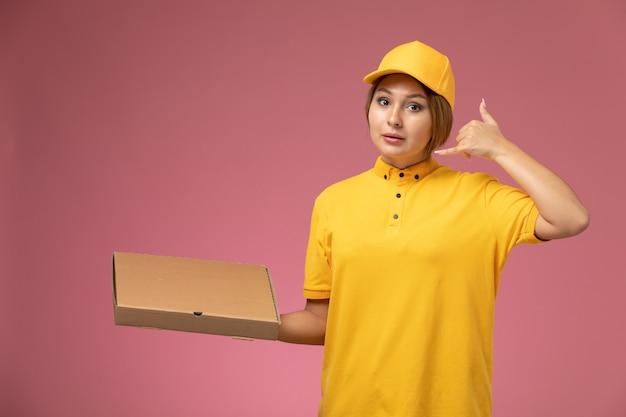 Corriere femminile di vista frontale nel pacchetto dell'alimento della tenuta del capo giallo uniforme giallo che mostra il gesto di telefonata sul colore del lavoro di consegna uniforme della scrivania rosa