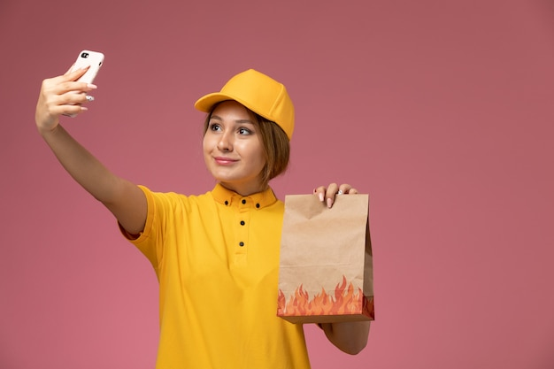Front view female courier in yellow uniform yellow cape holding food package taking selfie on pink background uniform delivery work color job