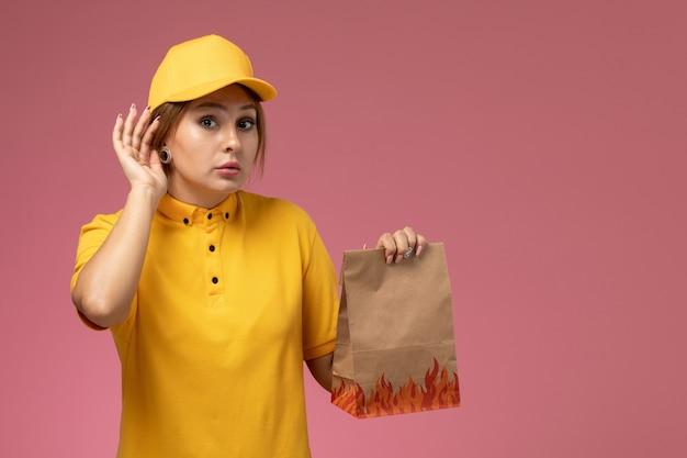 Corriere femminile di vista frontale in mantello giallo uniforme giallo che tiene il pacchetto di cibo cercando di ascoltare sul lavoro di lavoro di consegna uniforme sfondo rosa