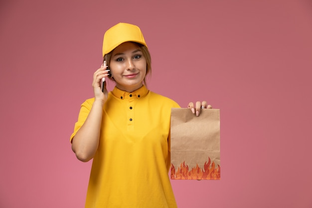 Front view female courier in yellow uniform yellow cape holding food package white talking on the phone on the pink desk uniform delivery work color job