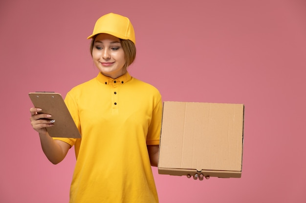 Front view female courier in yellow uniform yellow cape holding notepad and food package on the pink background uniform delivery work job