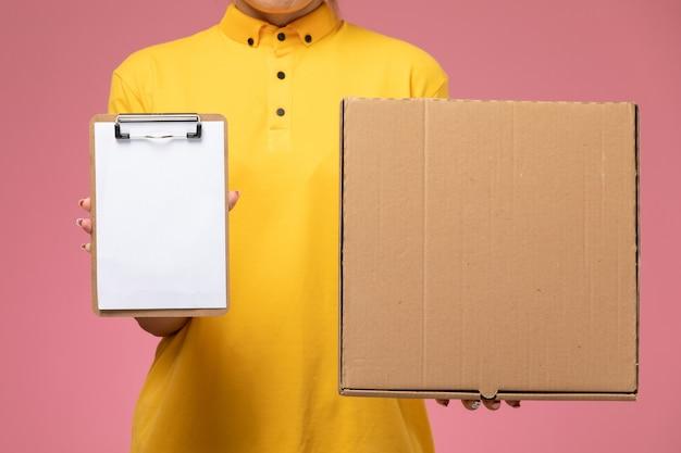 Corriere femminile di vista frontale in mantello giallo uniforme giallo che tiene il pacchetto dell'alimento del blocchetto per appunti sul colore del lavoro femminile di consegna uniforme della scrivania rosa