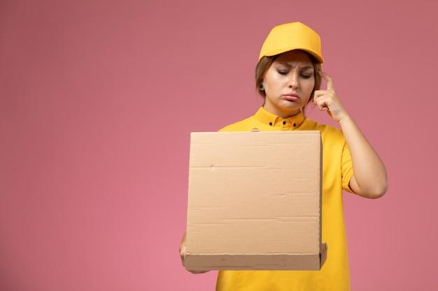 Corriere femminile di vista frontale in mantello giallo uniforme giallo che tiene e che apre la scatola di cibo sul colore femminile di consegna uniforme da scrivania rosa