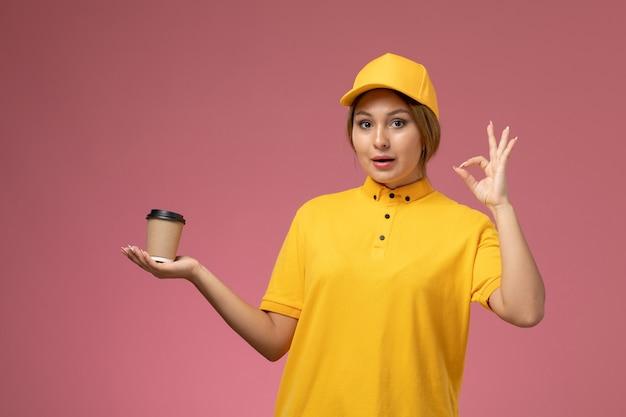 Corriere femminile di vista frontale nel mantello giallo uniforme giallo che tiene la tazza di caffè marrone di plastica sul colore femminile di consegna dell'uniforme rosa della scrivania