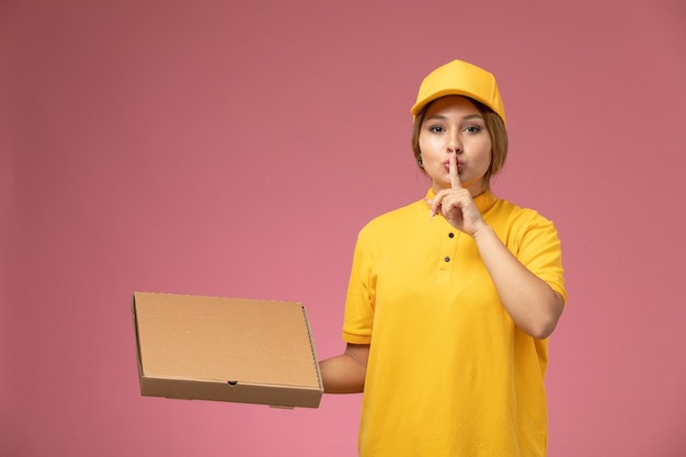 Front view female courier in yellow uniform yellow cape holding plastic brown coffee cup showing silence sign on the pink desk uniform delivery female color