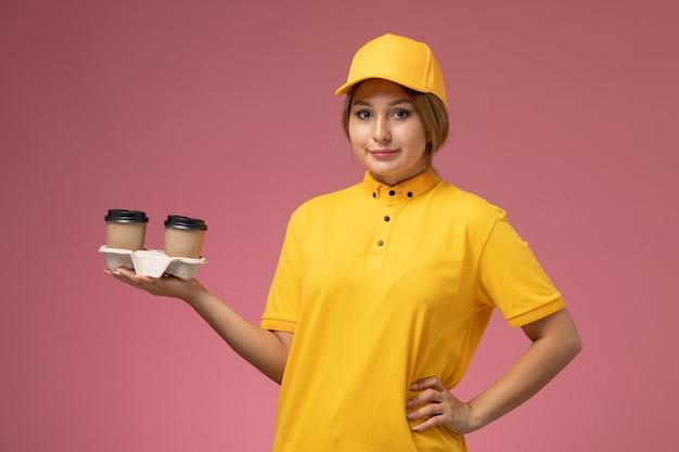 Corriere femminile di vista frontale nel mantello giallo uniforme giallo che tiene le tazze di caffè marroni di plastica sul colore femminile di consegna uniforme del fondo rosa