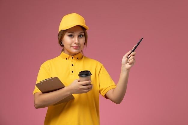 Corriere femminile di vista frontale in capo giallo uniforme giallo che tiene la penna del blocco note della tazza di caffè di plastica sul lavoro di lavoro di consegna uniforme del fondo rosa