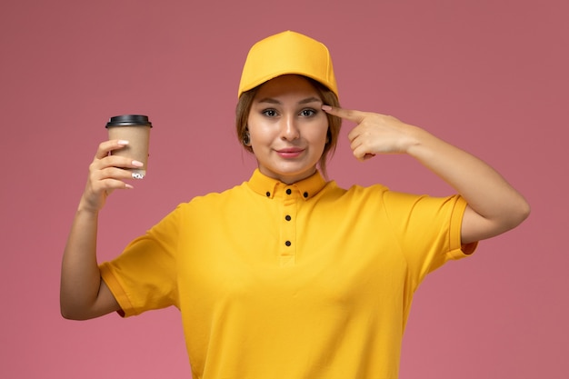 Front view female courier in yellow uniform yellow cape holding plastic coffee cup on the pink background uniform delivery job work