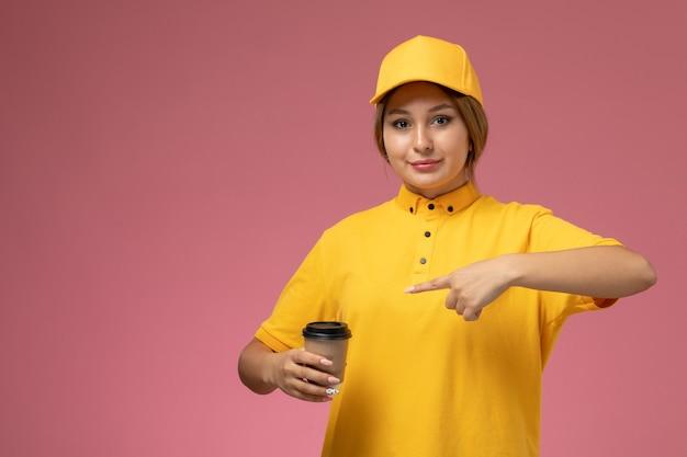 Corriere femminile di vista frontale in capo giallo uniforme giallo che tiene tazza di caffè di plastica sul lavoro di consegna uniforme sfondo rosa