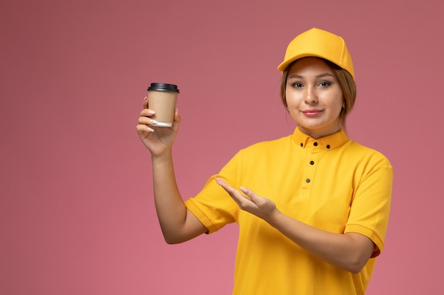 Front view female courier in yellow uniform yellow cape holding plastic coffee cup on the pink background uniform delivery work color