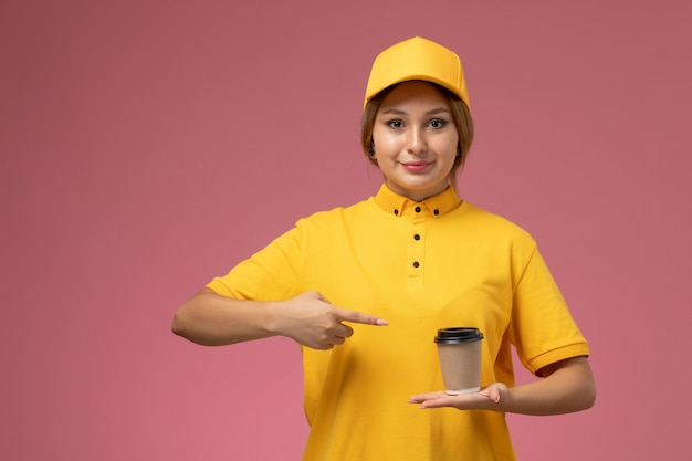 Front view female courier in yellow uniform yellow cape holding plastic coffee cup on pink background uniform delivery work job