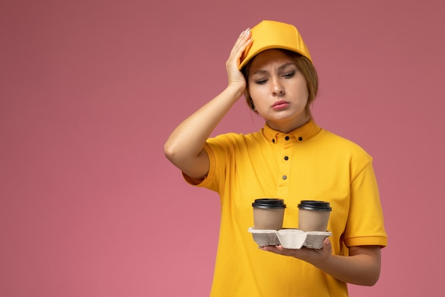 Front view female courier in yellow uniform yellow cape holding plastic coffee cups on pink background uniform delivery work