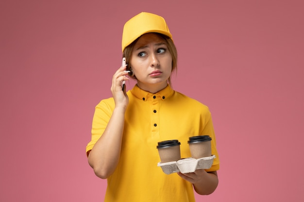 Front view female courier in yellow uniform yellow cape holding plastic coffee cups and talking on the phone on pink desk uniform delivery work color job
