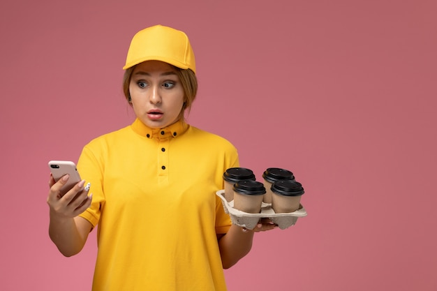 Front view female courier in yellow uniform yellow cape holding plastic coffee cups and white phone on pink background uniform delivery work color job