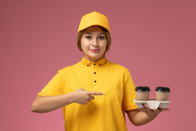 Front view female courier in yellow uniform yellow cape holding plastic coffee cups with smile on the pink background uniform delivery work job