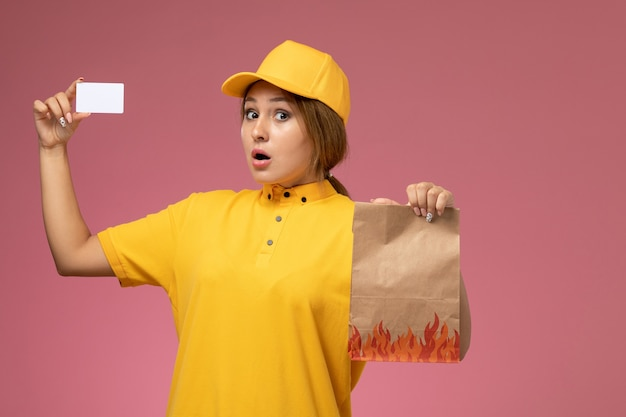 Front view female courier in yellow uniform yellow cape holding white card and food package on pink background uniform delivery work color photo female