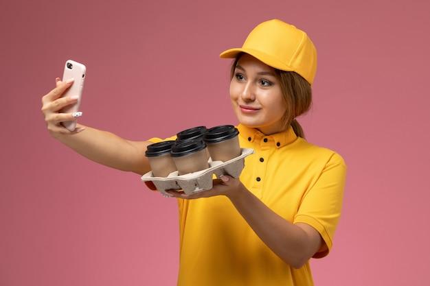 Corriere femminile di vista frontale in capo giallo uniforme giallo che prende un selfie con le tazze di caffè sul lavoro di colore del lavoro di consegna uniforme del fondo rosa