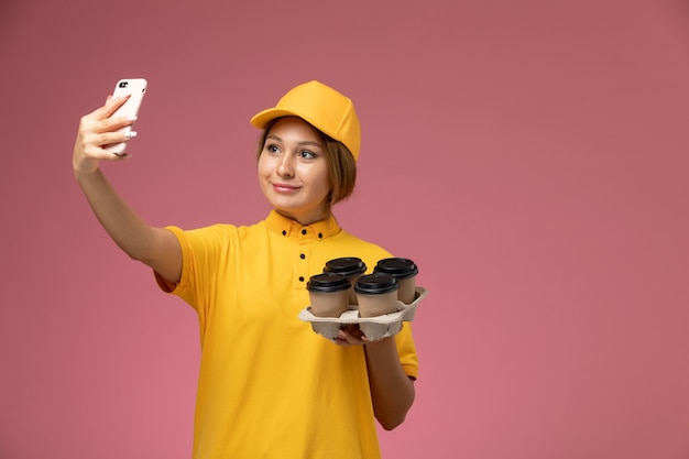 Corriere femminile di vista frontale in capo giallo uniforme giallo che prende un selfie con caffè sul lavoro di colore di lavoro di consegna uniforme del fondo rosa