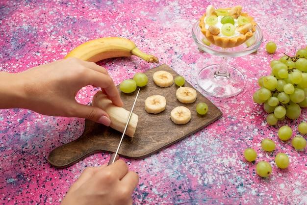 明るい表面のフルーツケーキの新鮮なまろやかな色のブドウと正面図女性切削バナナ