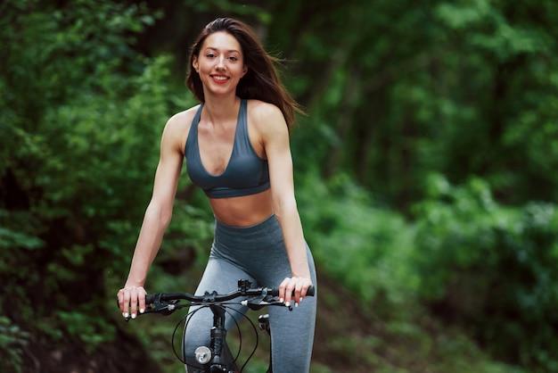 正面図。昼間の森の中のアスファルトの道路上の自転車の女性サイクリスト