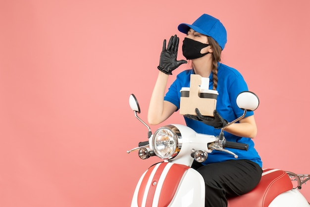 Front view of female delivery person wearing medical mask and gloves sitting on scooter delivering orders calling someone on pastel peach background