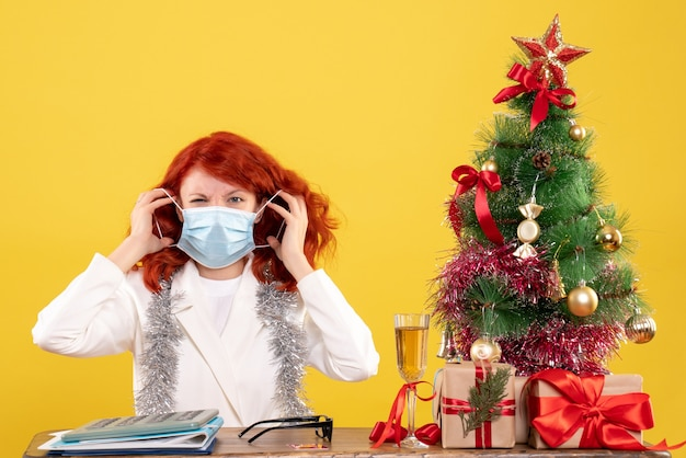 크리스마스 트리와 마스크에 앉아 선물 주위 전면보기 여성 의사