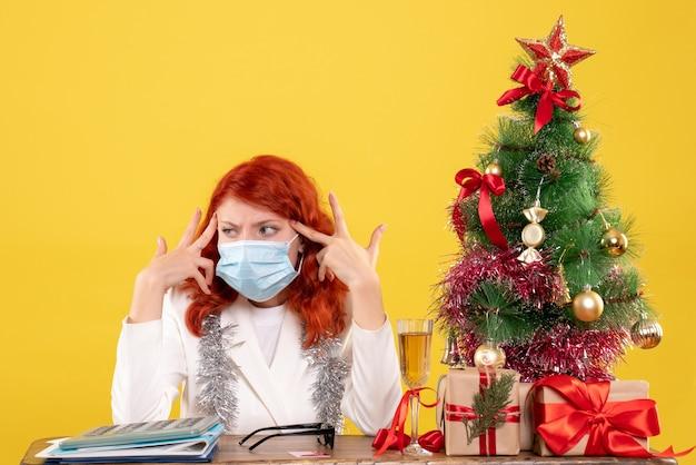 Medico femminile di vista frontale intorno all'albero di natale e regali che si siedono nella maschera