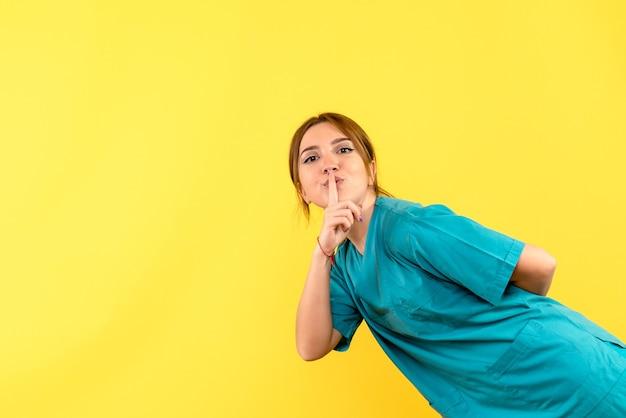 Medico femminile di vista frontale che chiede di tacere sullo spazio giallo
