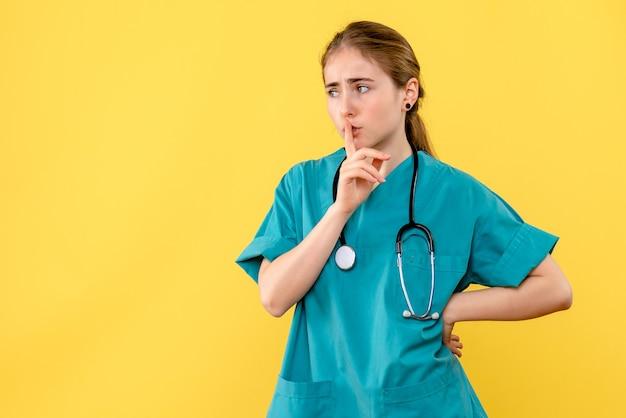 Medico femminile di vista frontale che chiede di mantenere il silenzio sulla salute dell'ospedale di emozione sfondo giallo