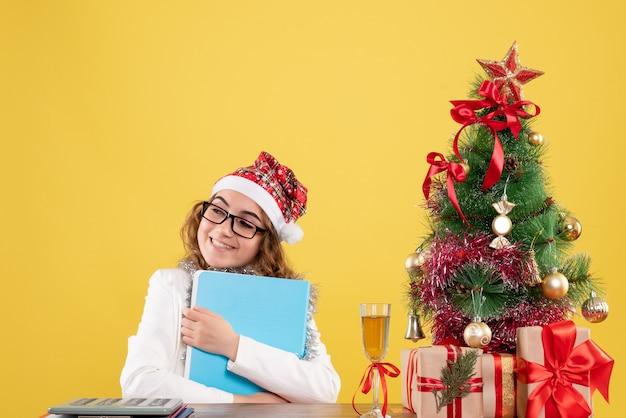 Вид спереди женщина-врач за столом, держащая файлы с улыбкой
