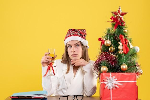 Medico femminile di vista frontale che celebra il natale con champagne