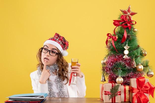 Medico femminile di vista frontale che celebra il natale con un bicchiere di champagne