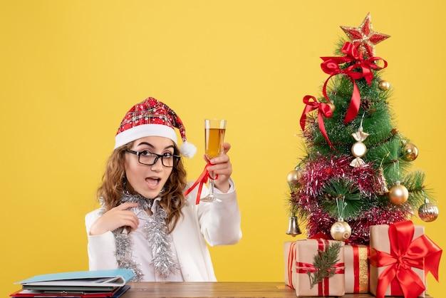 샴페인 잔으로 크리스마스를 축 하하는 전면보기 여성 의사