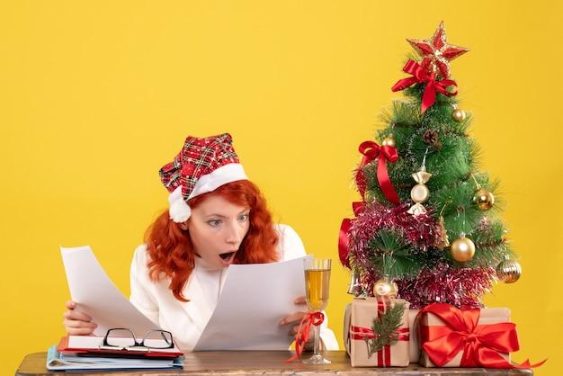 Medico femminile di vista frontale che controlla i documenti dietro il tavolo con i regali